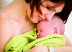 Mother holding sleeping baby girl
